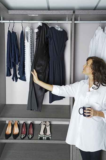 Beautiful young woman choosing an outfit from her organized wardrobe closet