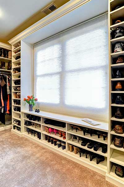 Master walk in closet with vertcial shoe shelves around picture window