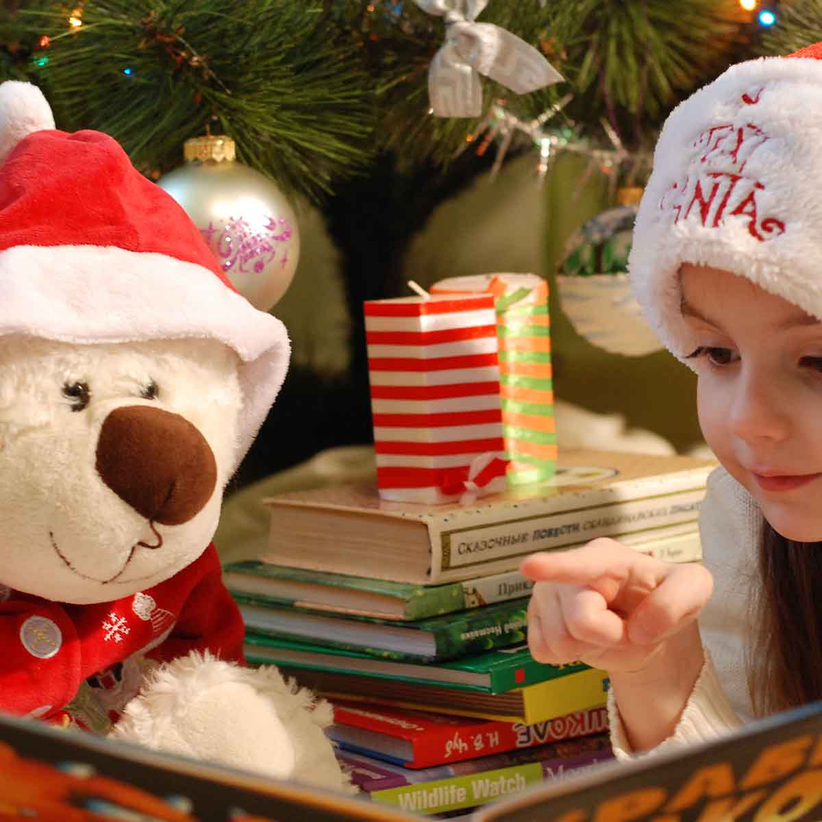 adorable girl reading books in front of christmas tree with teddy bear