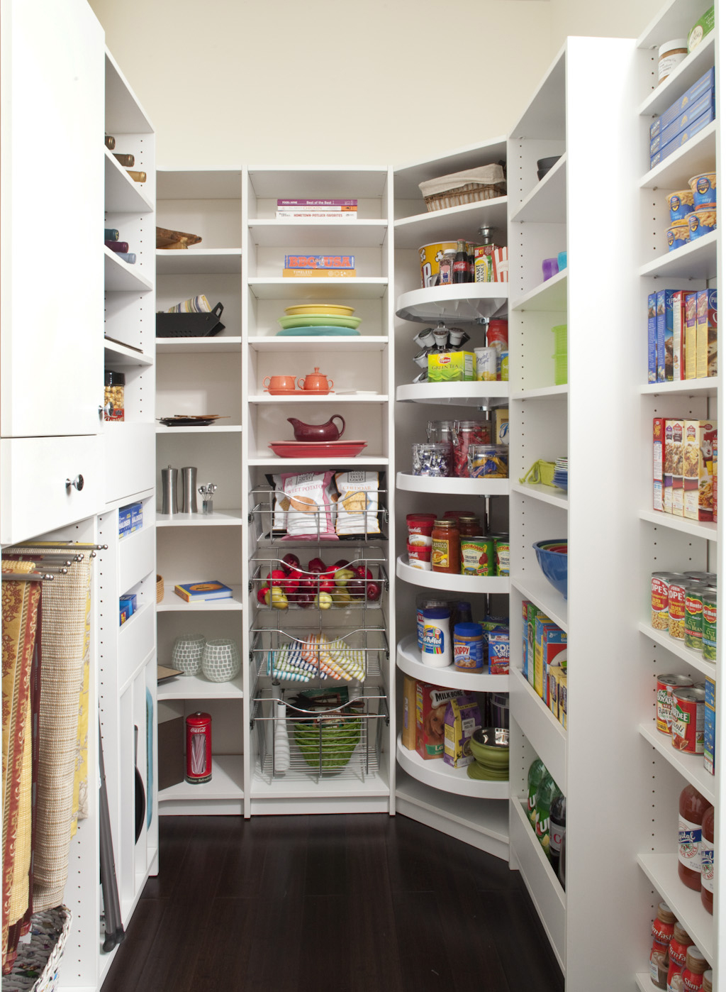 Pantry orgnized with various items on custom shelving and Lazy Susan